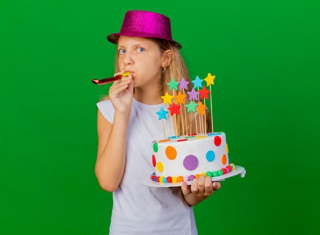 Niña bonita en sombrero de fiesta con pastel de cumpleaños que sopla el silbato