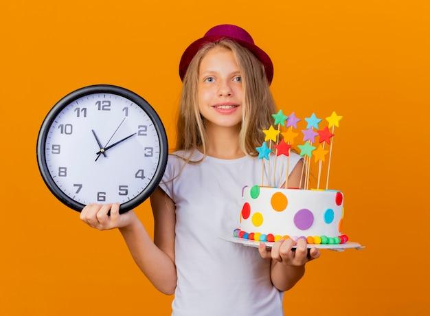 Niña bonita con sombrero de fiesta con pastel de cumpleaños y reloj de pared sonriendo con cara feliz, concepto de fiesta de cumpleaños