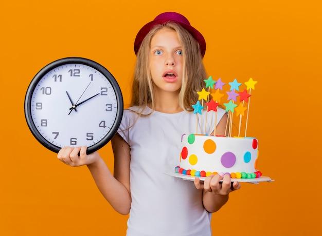 Niña bonita con sombrero de fiesta con pastel de cumpleaños y reloj de pared sorprendido, concepto de fiesta de cumpleaños