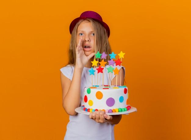 Niña bonita con sombrero de fiesta sosteniendo pastel de cumpleaños mirando sorprendido llamando a alguien, concepto de fiesta de cumpleaños