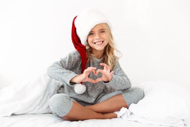 Niña bonita con sombrero de santa que muestra el signo del corazón mientras está sentado con las piernas cruzadas en la cama blanca