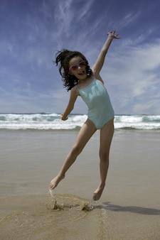 Niña bonita sonriendo mientras juega saltando en la orilla de la playa