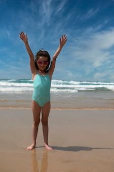 Niña bonita sonriendo mientras jugaba en la orilla del mar en fuerteventura