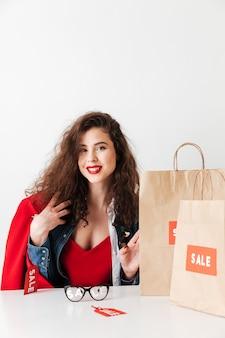 Niña bonita sonriente compradora compulsiva sentado con bolsas de papel
