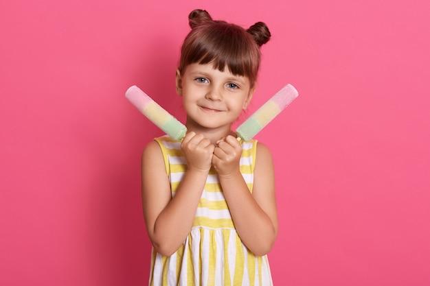 Niña bonita sosteniendo un gran helado, la niña se ve feliz, vestida con un vestido de rayas amarillas y blancas, con dos moños divertidos.