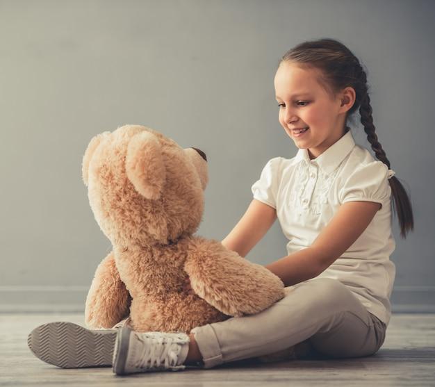 Niña bonita está sosteniendo un oso de peluche.