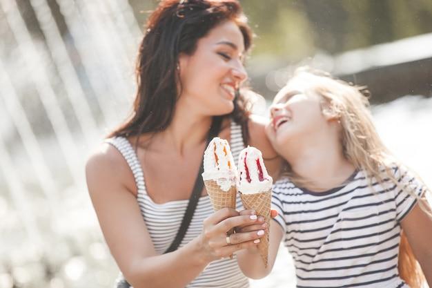 Niña bonita con su madre comiendo helado