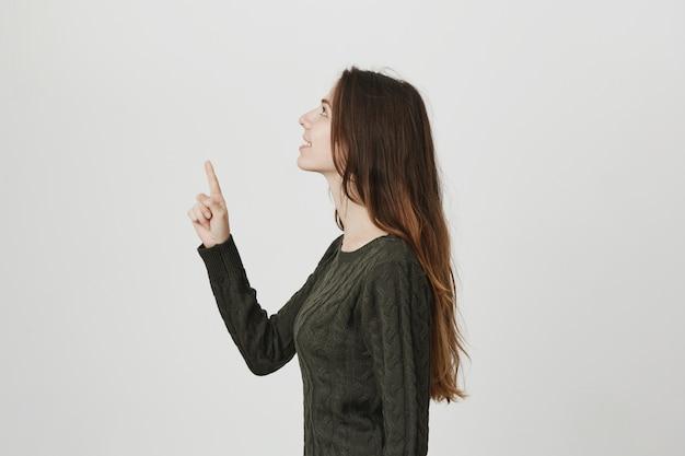 Niña bonita en suéter, perfil de pie, levantar la cabeza y apuntando hacia arriba