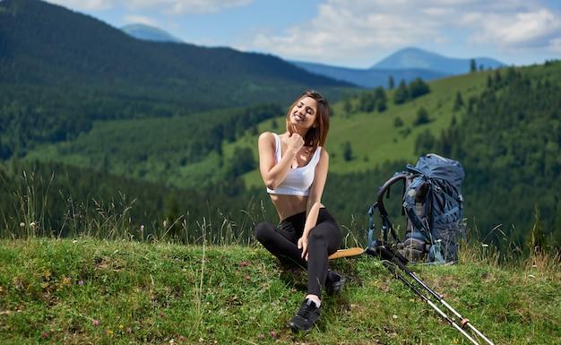 Niña bonita turista con mochila y bastones de trekking sentado con los ojos cerrados