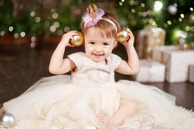 Niña bonita en vestido blanco jugando y siendo feliz con el árbol de navidad y las luces.