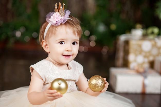 Niña bonita en vestido blanco jugando y siendo feliz con las luces de navidad