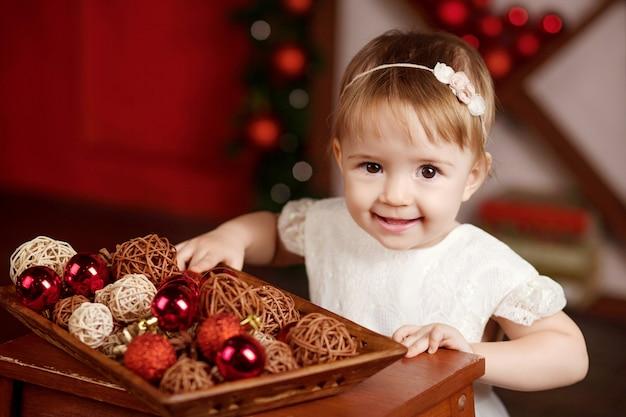 Niña bonita en vestido blanco jugando y siendo feliz con las luces de navidad.