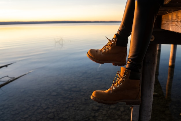 Niña con botas sentado en un muelle durante la puesta de sol