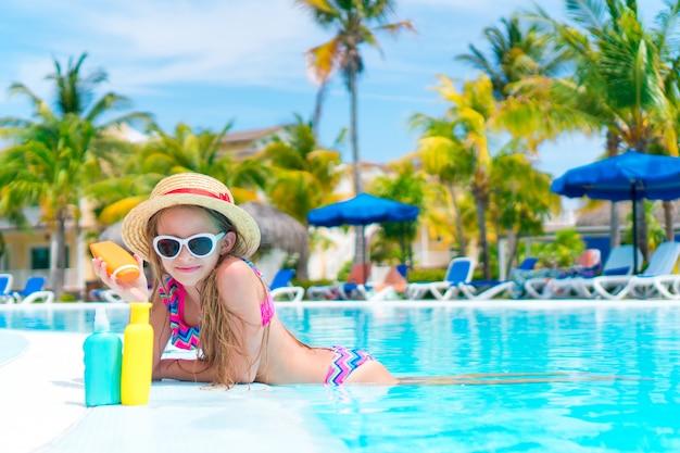 Niña con botella de crema solar en piscina