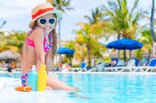 Niña con una botella de crema solar sentado en el borde de la piscina