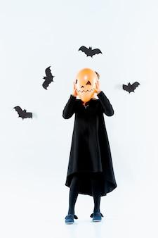 Niña bruja en vestido largo negro y accesorios mágicos