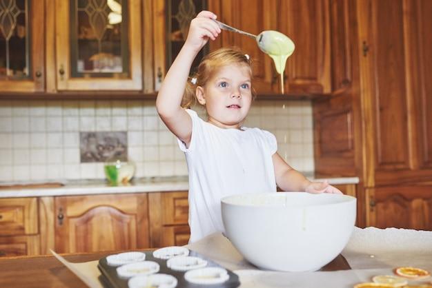 Una niña buena hornea sabrosos pastelitos