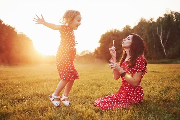Niña con burbujas con su madre en el parque al atardecer.