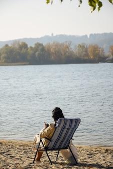 Una niña con cabello negro se sienta en la orilla de un río en una tumbona y mira a un teléfono móvil