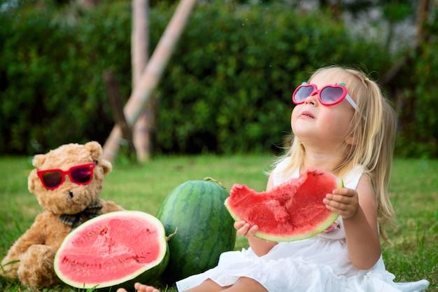 Niña con cabello rubio en gafas de sol comiendo sandía en el parque, al siguiente oso de peluche sentado