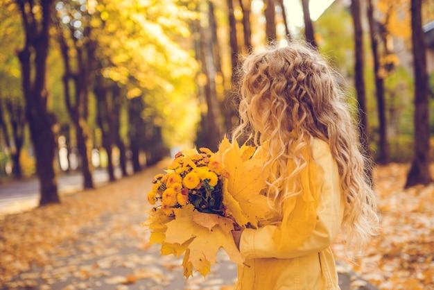 Niña con cabello rubio en otoño con flores amarillas