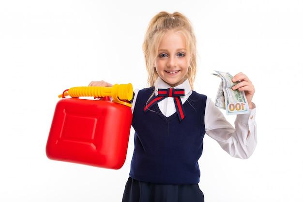 Una niña con cabello rubio relleno en una cola de caballo tiene dinero y una lata de juguete