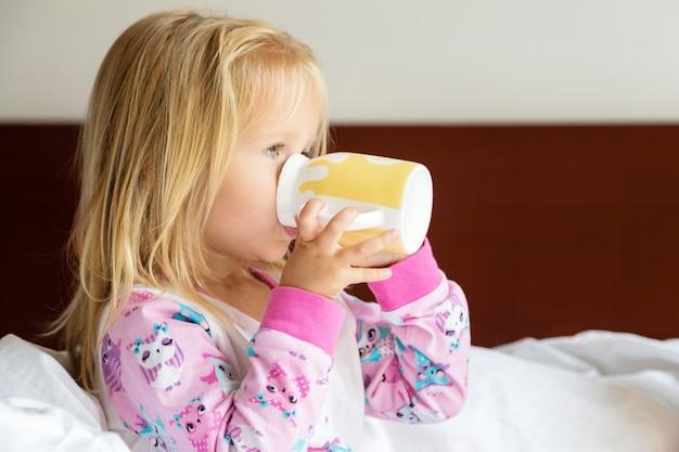 Niña con cabello rubio sentada en la cama y bebiendo leche