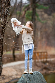 Niña con un cachorro blanco. un cachorro en manos de una niña