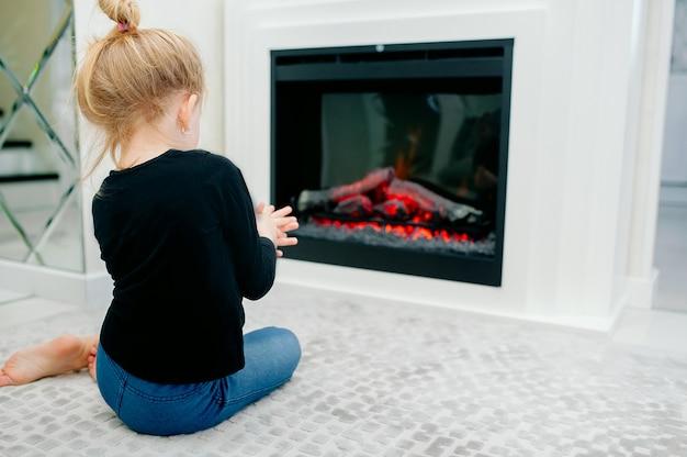 Niña calienta sus manos junto a la chimenea en una acogedora habitación en casa