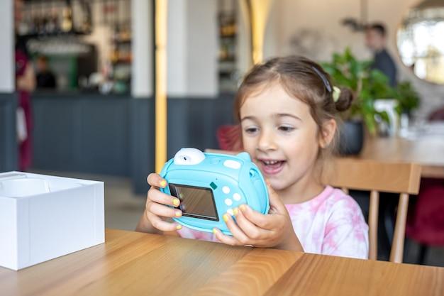 Una niña y una cámara para niños para la impresión instantánea de fotografías.