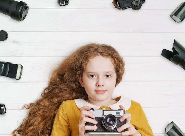 Niña con cámaras de fotos retro y accesorios de fotos sobre un piso de madera.