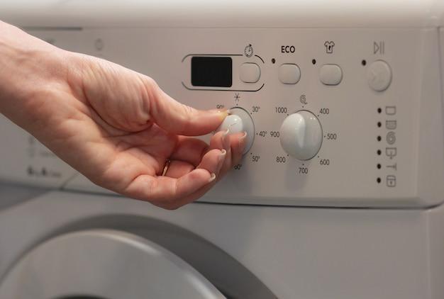 La niña cambia la temperatura en la lavadora.