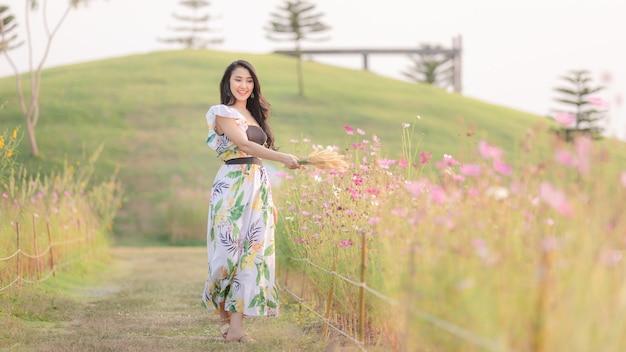La niña camina alegremente en el jardín de flores en la mano sosteniendo la hierba