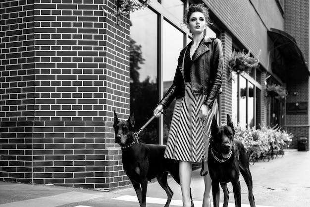 Una niña camina por la calle de la ciudad a lo largo del edificio con dos dobermans con una correa