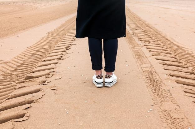 Niña camina por el camino de arena hacia el mar con viento y lluvia