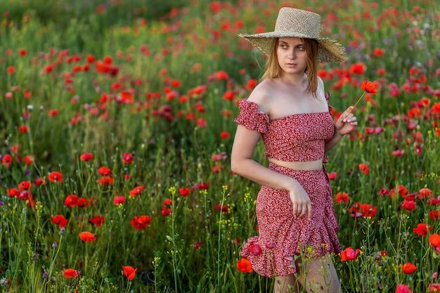 Una niña camina en un campo de amapolas. con vestido rojo y sombrero de paja.