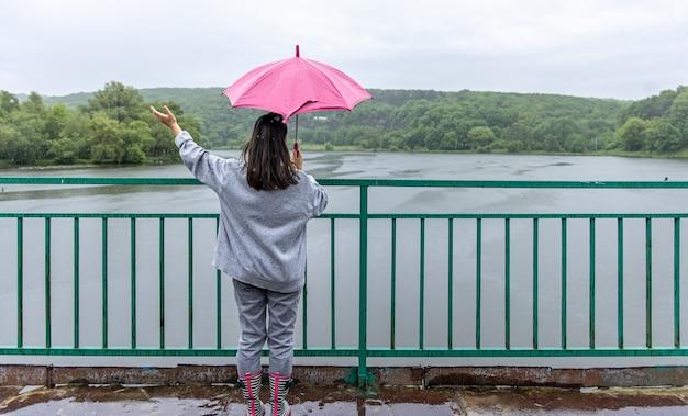 Una niña camina bajo un paraguas en tiempo lluvioso en un puente en el bosque.