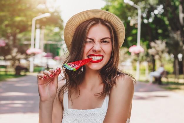 Una niña camina en el parque con una paleta riéndose y haciendo una mueca. encantadora niña come piruleta y arruga su nariz