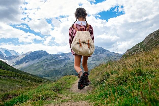 Niña camina por sendero de montaña durante una excursión. con la mochila