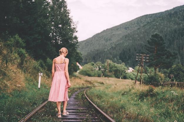 Niña caminando en el ferrocarril. mujer en vestido rosa caminando por las vías del ferrocarril.