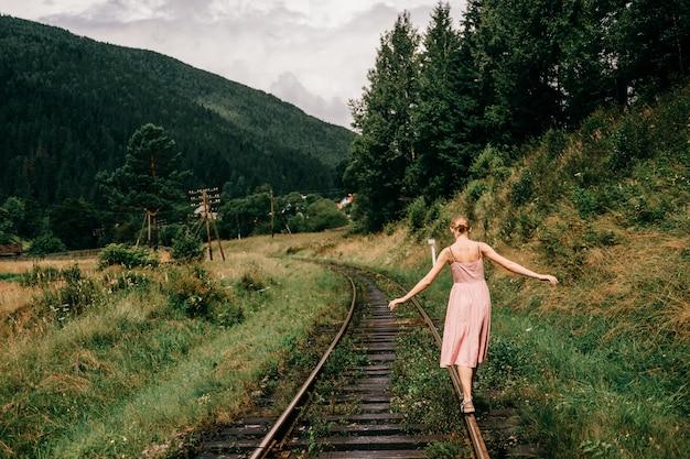 Niña caminando en el ferrocarril