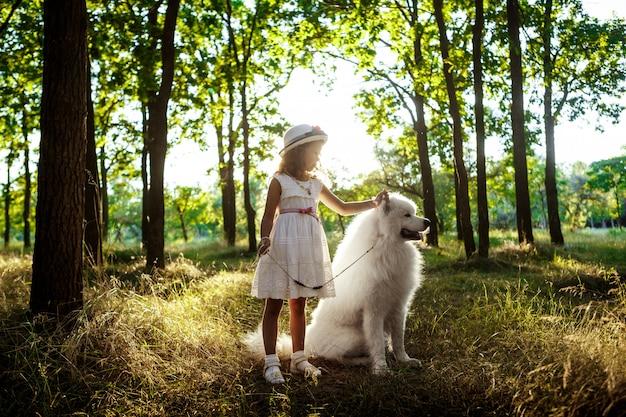 Niña caminando, jugando con el perro en el parque al atardecer.