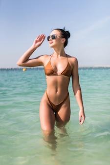 Una niña caminando en el mar en bikini y disfrutando del sol