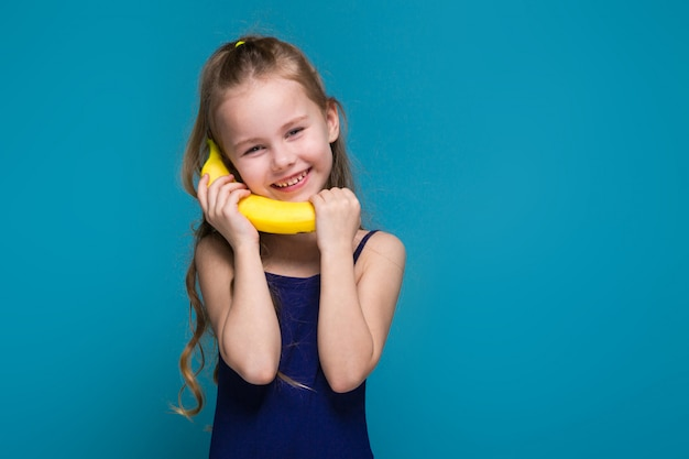 Niña en camisa con brunet pelo sostener un plátano