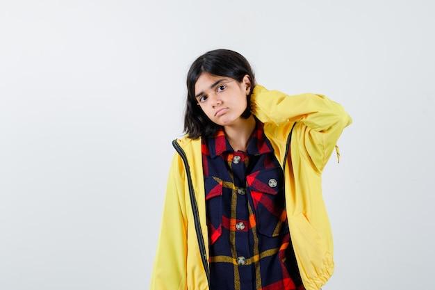 Niña en camisa a cuadros, chaqueta sosteniendo la mano en el cuello y mirando fatigado, vista frontal.