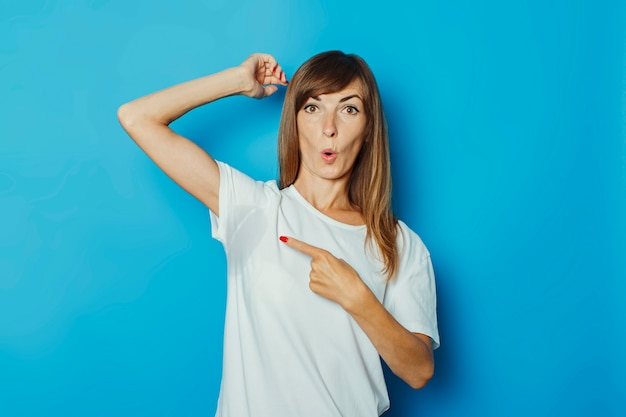 Niña con una camiseta blanca muestra un dedo en las axilas húmedas de sudor sobre un fondo azul.