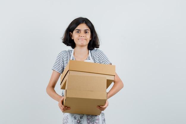 Niña en camiseta, delantal con cajas de cartón,