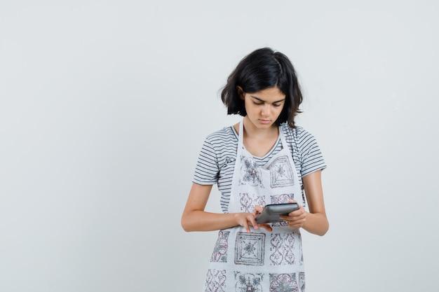 Niña en camiseta, delantal con calculadora y mirando ocupado,
