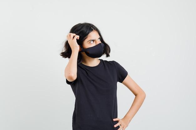 Niña en camiseta negra, máscara rascándose la cabeza y mirando pensativa, vista frontal.