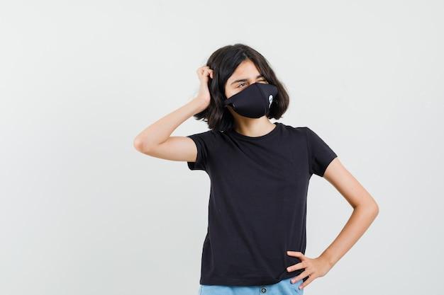 Niña en camiseta negra, pantalones cortos, máscara rascándose la cabeza, mirando hacia arriba y mirando pensativo, vista frontal.
